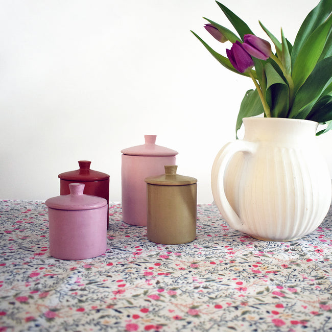 Handmade canister on pink flowers linen tablecloth creates a Colorful Home Decor and colorful tablescapes - Collyer's Mansion