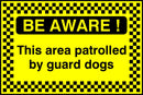 BE AWARE! This area patrolled by guard dogs. Sign