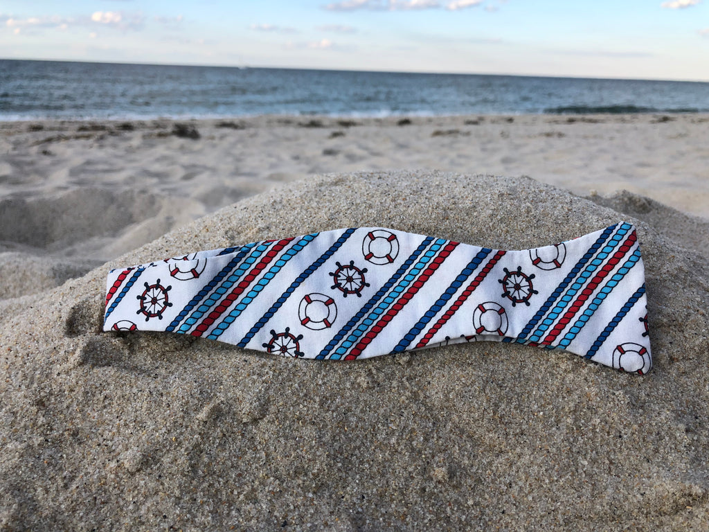 White bow tie with red white and blue colored ships wheels and rope