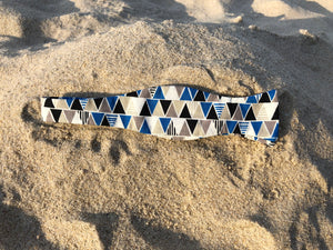 Blue, white, black and grey pyramids on a bow tie
