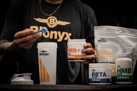 sports nutrition supplements poured into shaker bottle
