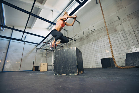Female athlete doing box jumps in a crossfit gym
