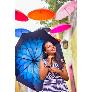 Smiling Woman with blue floral umbrella looking up at umbrellas overhead