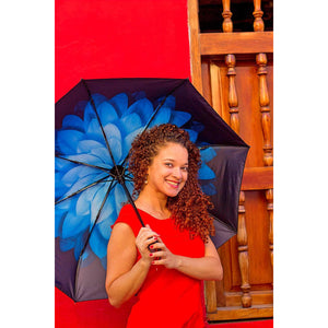 Smiling woman with curly hair and blue floral umbrella in front of red wall