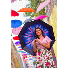 Load image into Gallery viewer, Smiling lady holding umbrella with purple flower with umbrellas above