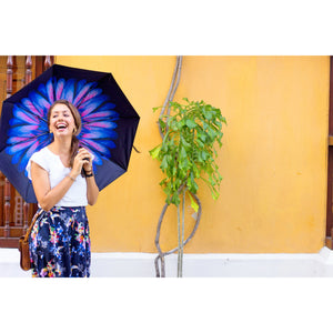 Woman laughing holding umbrella with purple flower with yellow wall in background