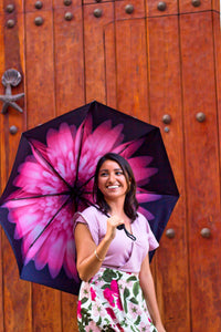 Woman smiling holding pink floral umbrella; uv umbrella in front of wooden door