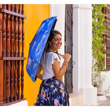 Load image into Gallery viewer, Smiling woman holding blue Umbrella with blue skies design with colonial yellow wall background