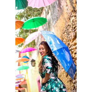 Smiling woman holding blue umbrella under row of umbrellas