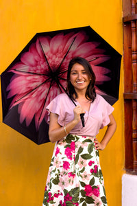 Woman smiling holding pink floral umbrella; uv umbrella
