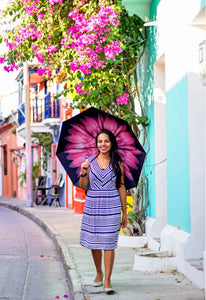 Smiling woman walking with pink floral umbrella and flowers in background