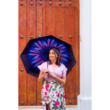 Load image into Gallery viewer, Woman smiling holding purple floral umbrella in front of wooden door; uv umbrella