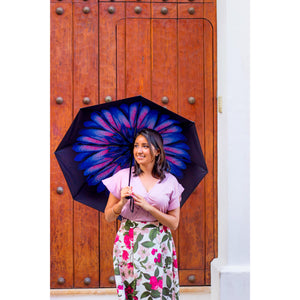 Woman smiling holding purple floral umbrella in front of wooden door; uv umbrella