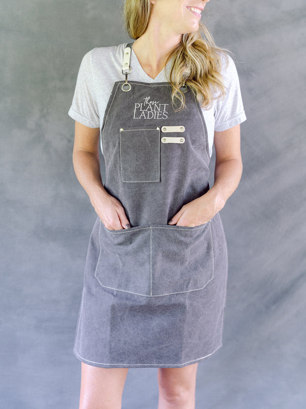 Model wearing grey garden apron with Those Plant Ladies logo. Includes 3 pockets and pen clip.