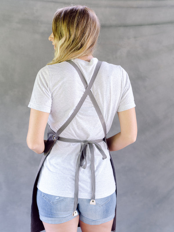 Back of grey garden apron: criss-cross straps with tie at the waist.