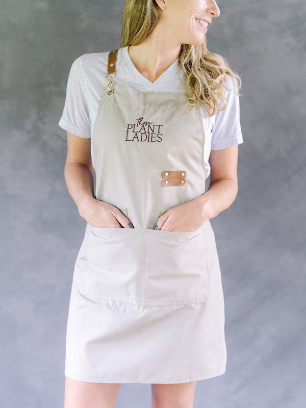 Model wearing cream garden apron with Those Plant Ladies logo. Includes 3 pockets and pen clip.