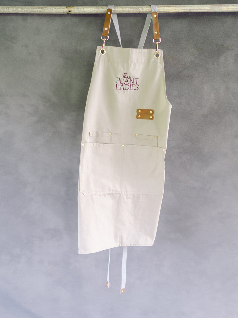 Cream garden apron with Those Plant Ladies logo, hanging. Includes 3 pockets and pen clip.