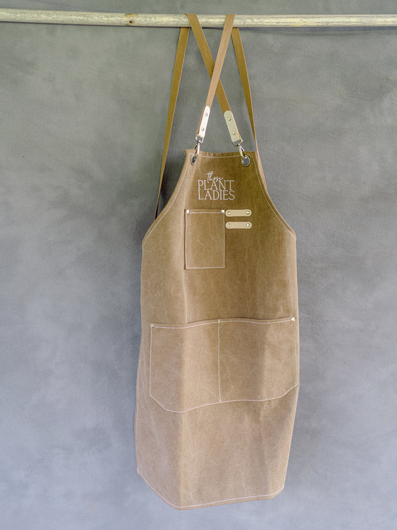 Brown garden apron with Those Plant Ladies logo, hanging. Includes 3 pockets and pen clip.