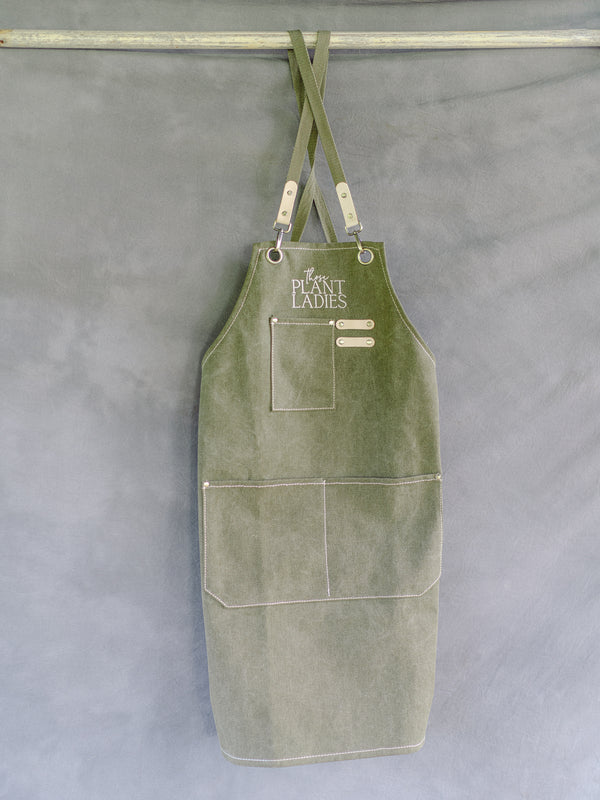 Green garden apron with Those Plant Ladies logo, hanging. Includes 3 pockets and pen clip.
