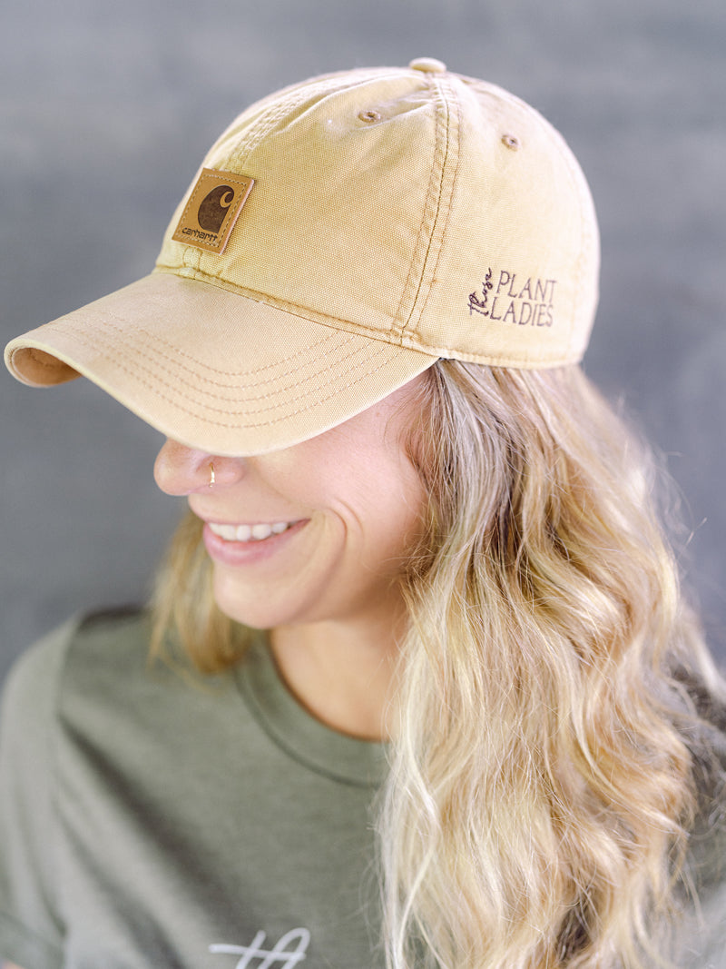 Model wearing brown carhartt cap with Those Plant Ladies logo embroidered on the left side; adjustable opening in back. Side view of model.