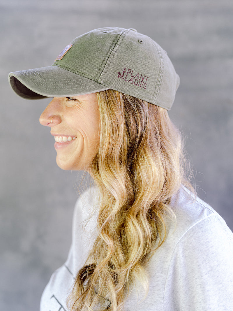 Model wearing green carhartt cap with Those Plant Ladies logo embroidered on the left side; adjustable opening in back. Side view of model.