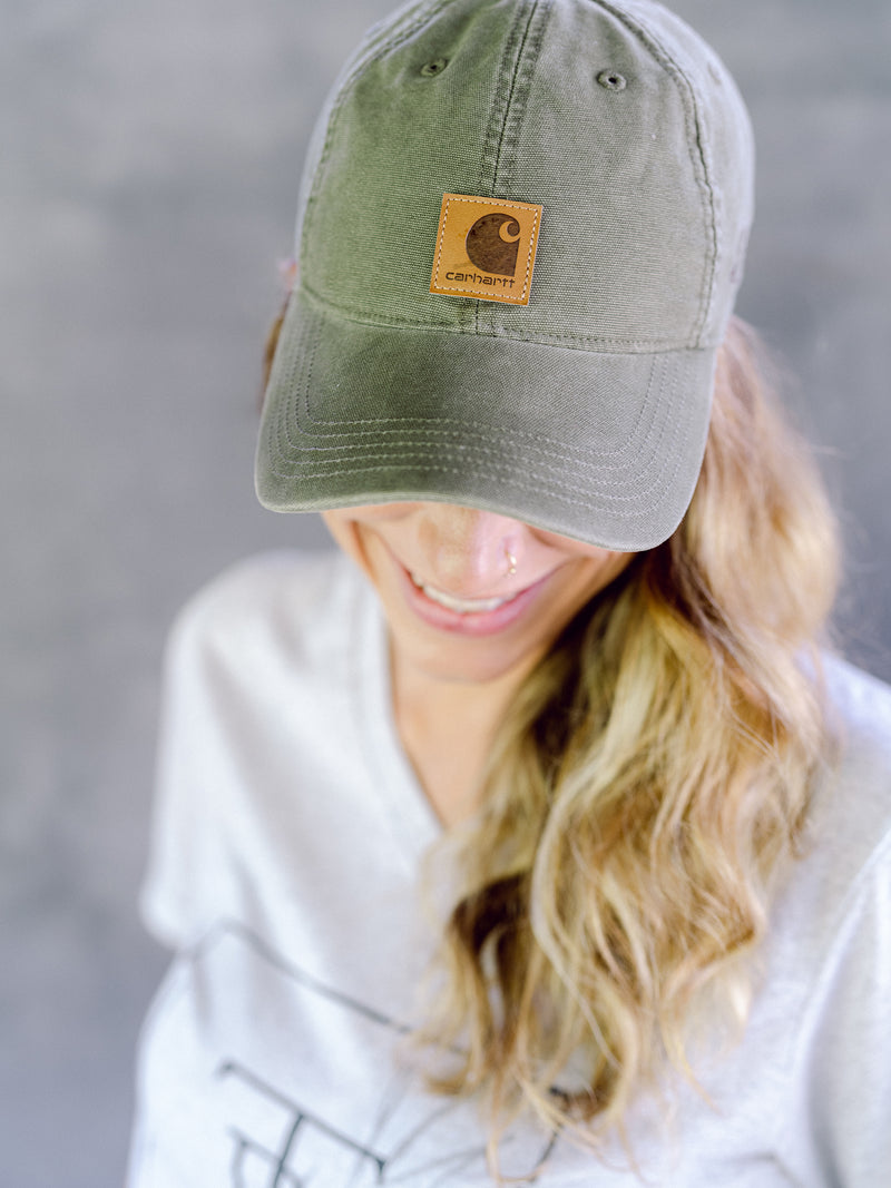Model wearing green Carhartt cap with Those Plant Ladies logo embroidered on the left side; adjustable opening in back. Front view of hat.