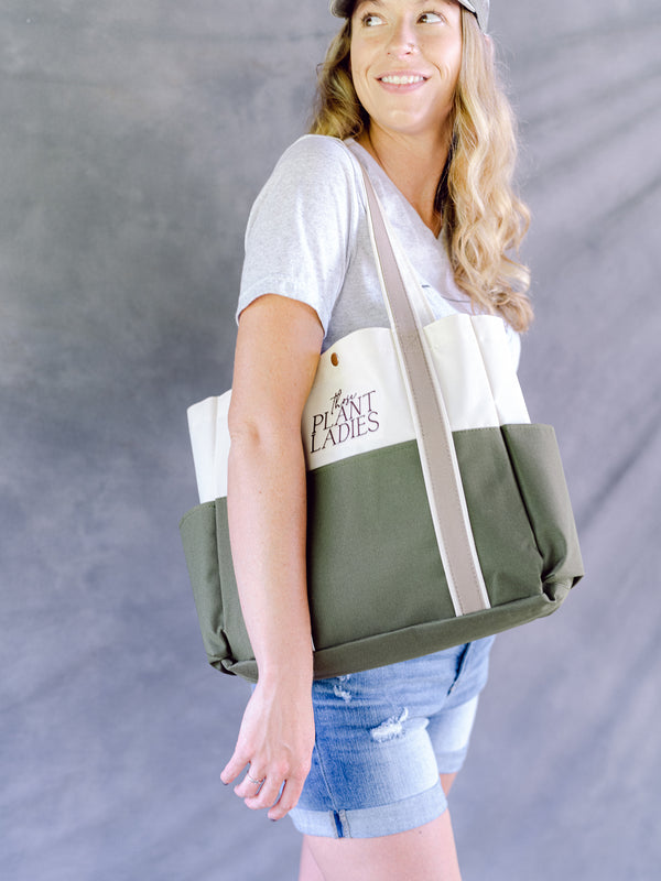 Model carrying garden tote bag; embroidered with Those Plant Ladies; green, tan, cream.
