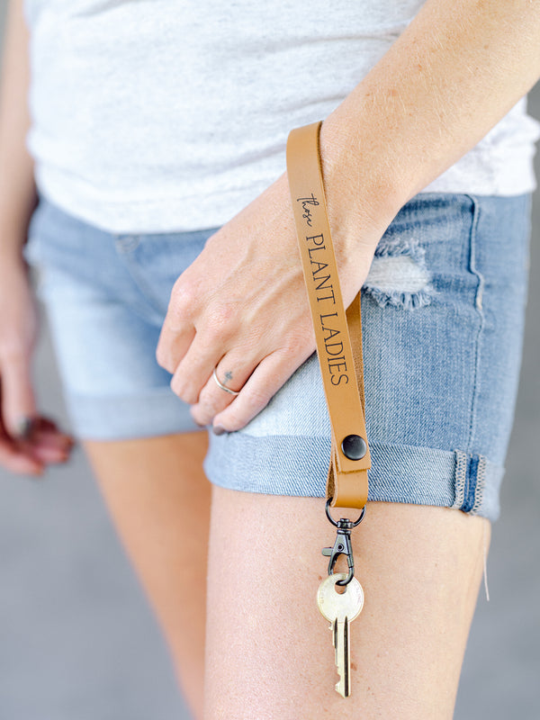 Model wearing brown wristlet with Those Plant Ladies logo.