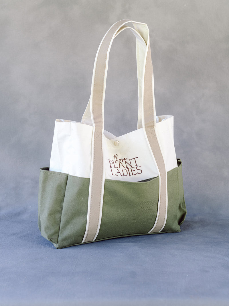 Garden bag with exterior pockets; embroidered with Those Plant Ladies; green, tan, cream.