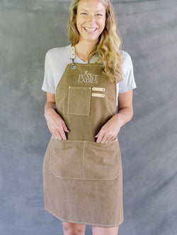 Model wearing brown garden apron with Those Plant Ladies logo. Includes 3 pockets and pen clip.