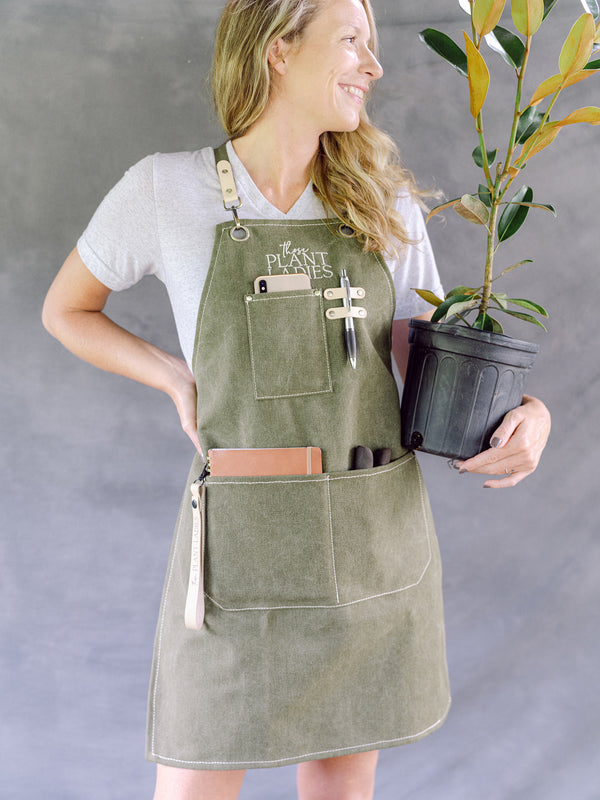 Model wearing green garden apron with Those Plant Ladies logo. Includes 3 pockets and pen clip.