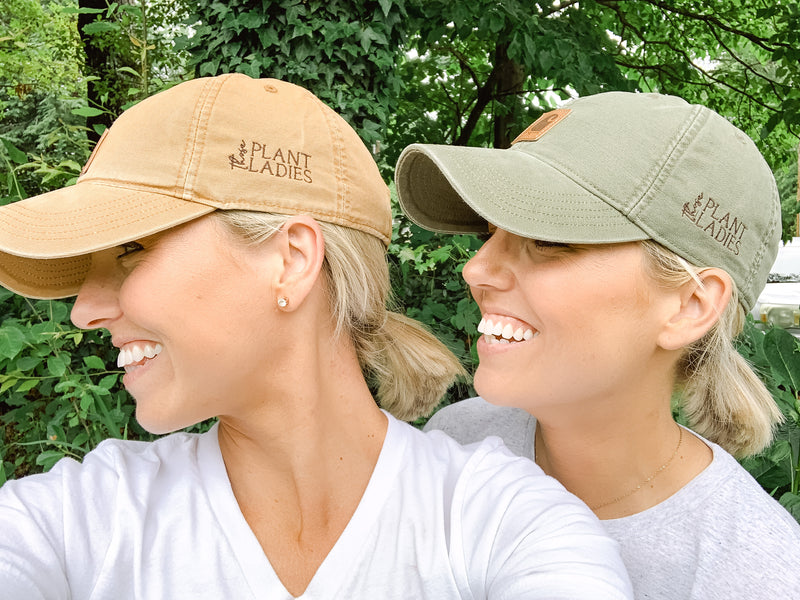 Those Plant Ladies green and brown Carhartt caps with Those Plant Ladies logo on the left side. Fawn and Heather, twins, view from the side.