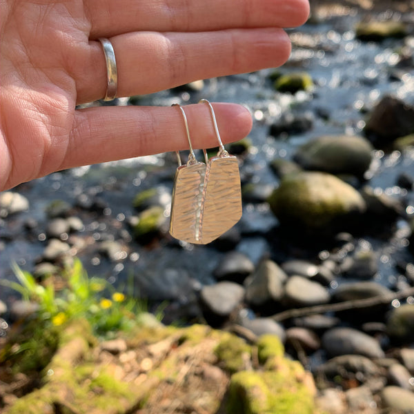 River collection silver dangle earrings on finger