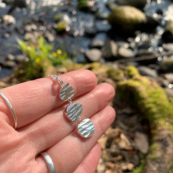 river collection necklace outdoors on hand
