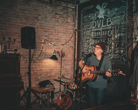 Richard Garvey, man singing and playing guitar, exposed brick wall, writing on the chalk wall, Death Valley's Little Brother as the venue