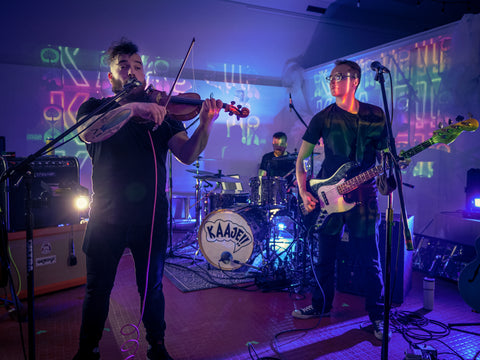 KAAJE!! band members performing on stage, one playing a guitar, one playing a violin, blue lights, green lights, pink lights are being reflected in the background