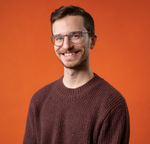 Adrian smiling in front of an orange background