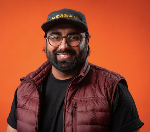Amit smiling in front of orange background