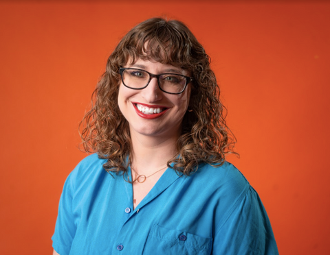 Kat smiling in front of orange background