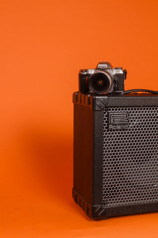 camera sitting on top of a speaker with an orange back ground