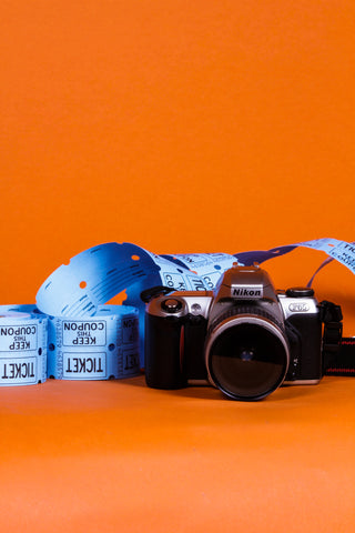 camera and blue tickets displayed in front of orange background