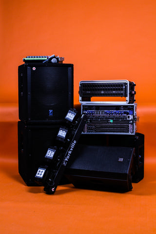 event and sound production equipment displayed in front of orange background