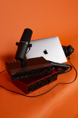 laptop, sound system and microphone displayed in front of orange background