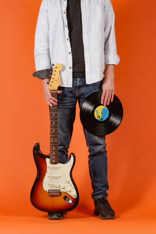 person holding a guitar and a record standing in front of an orange background