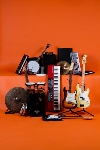 keyboards, guitars, amps, percussion instruments arranged in front of an orange background