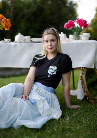 a girl sitting in the grass with a black limited run t-shirt