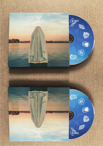 two CDS with half of the blue CD coming out of the package being displayed on a beige back drop