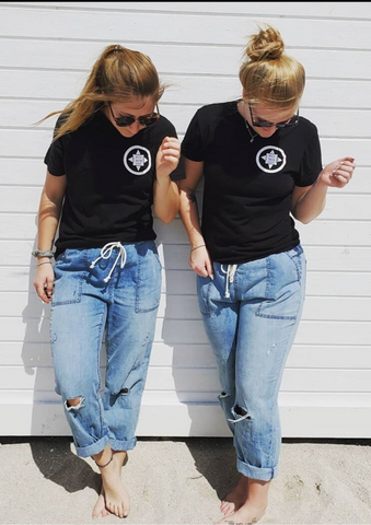 two girls wearing black North Coast Logo T-Shirts standing in front of a white back drop