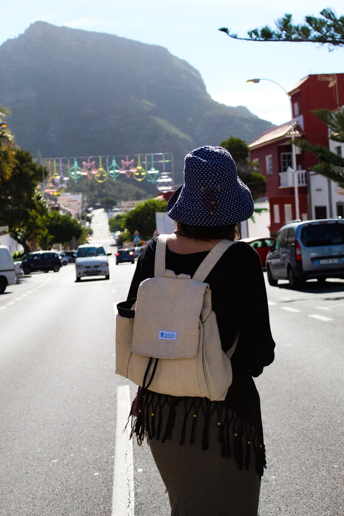 I am standing in the middle of a street wearing my backpack. It's a small sunny town in the Tenerife island