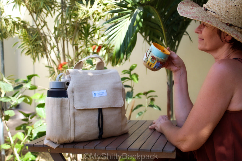 In this photo I am sitting at a wood table in my front yard, sipping of a cup of coffee. I bought this colorful mug in Colombia. It shows a typical Colombian village on a background of blue sky. It is beautiful. My backpack is set on the table.